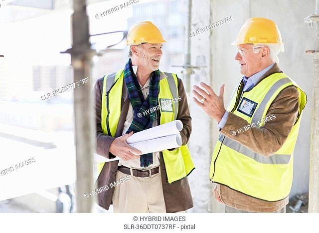 Businessman and worker talking on site