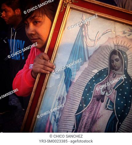 A pilgrim holds an image of the Virgin of Guadlaupe during the annual pilgrimage to the Our Lady of Guadalupe basilica in Mexico City, Mexico