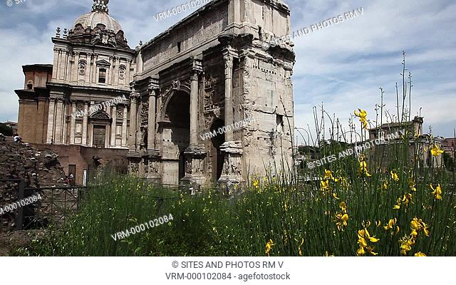 TILT up. Daylight. The Arch of Septimius Severus, with the Church of st. Luca and St. Martina in the background. The Arch was erected in 203 AD in honor of...