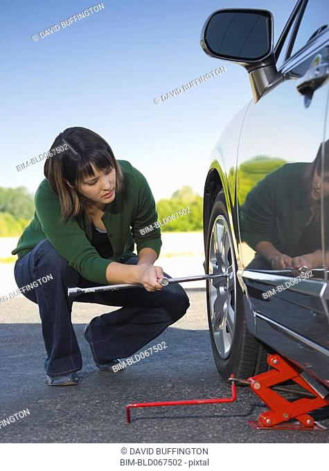 Asian woman changing car tire