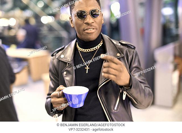 young fancy man holding coffee cup and gesticulating, African descent, in Munich, Germany