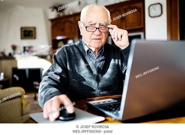 Portrait of senior man with laptop at home