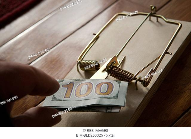 Hand of Hispanic man placing money in mousetrap