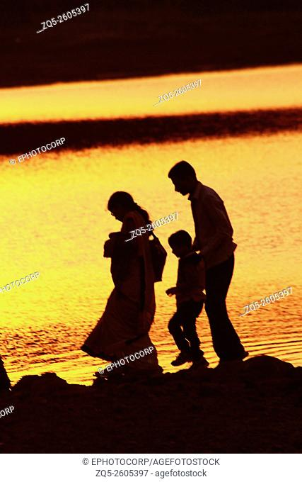 Silhouette of family of man, woman and child walking, Pune, India