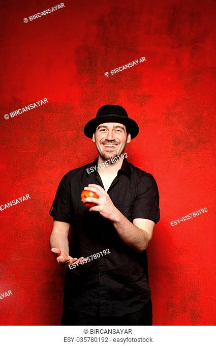 Young man juggling on a red background