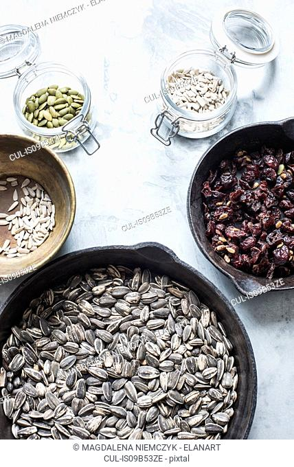 Studio shot, overhead view of dried fruit and seeds in pans and jars