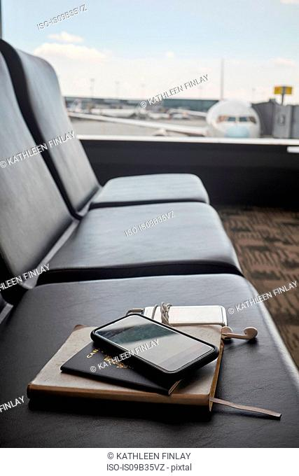 Passport and smartphone on seat in airport lounge