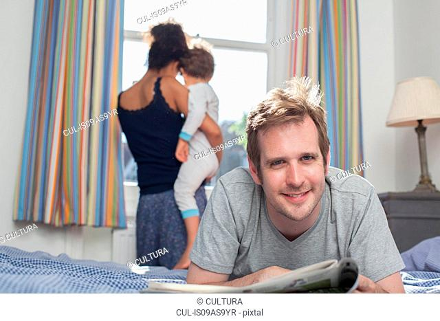 Mother and son looking out of window, father lying on bed reading newspaper