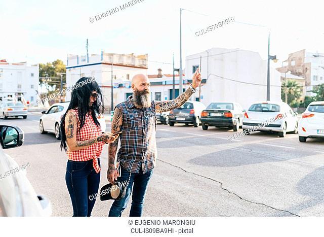 Mature hipster couple hailing a cab, Valencia, Spain
