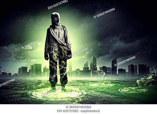 Man in respirator against nuclear background touching symbol. Pollution concept