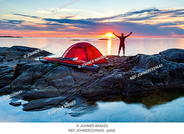 Man standing on rocks by tent