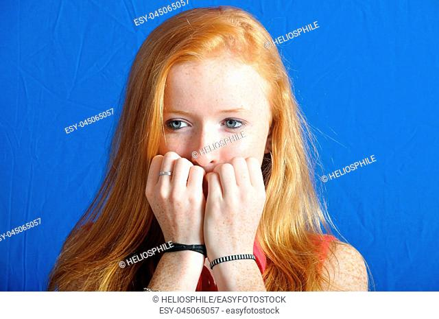 Scared teen on blue background