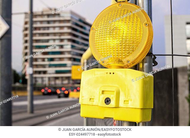 Construction site hazard warning light on urban cityscape