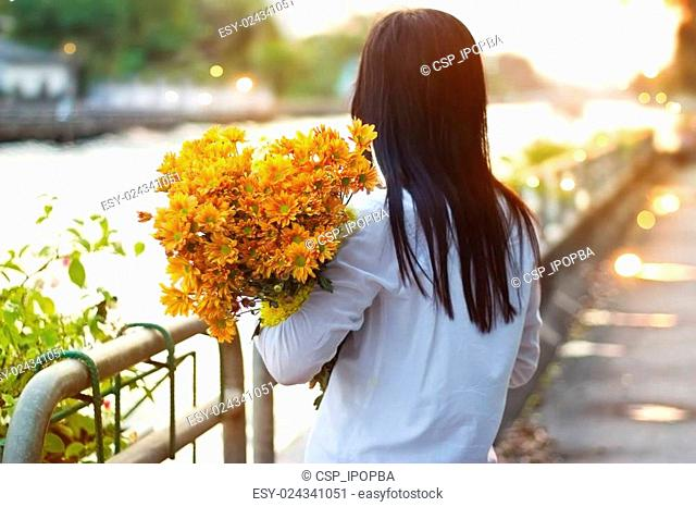 abstract woman with bouquet flowers vibrant in hands on street and canal sunset background, warm tone, focus on flowers, soft focus and blur