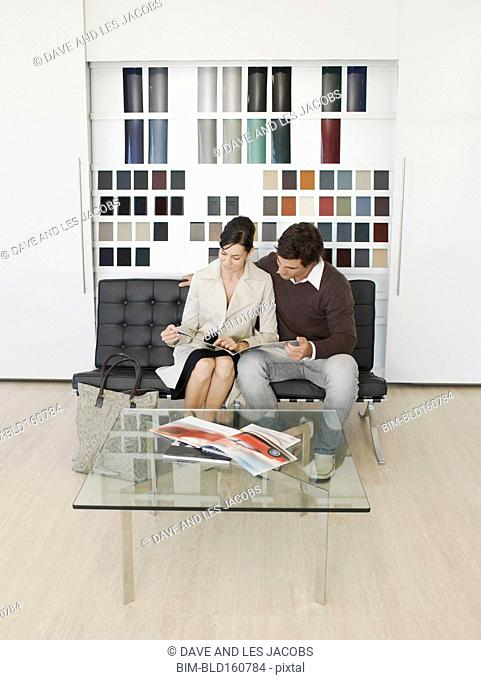 Caucasian couple reading brochure in car dealership