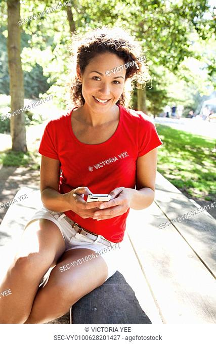 Portrait of woman with smart phone in park