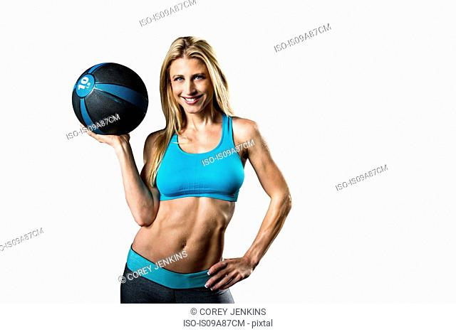Portrait of young woman holding medicine ball, studio shot