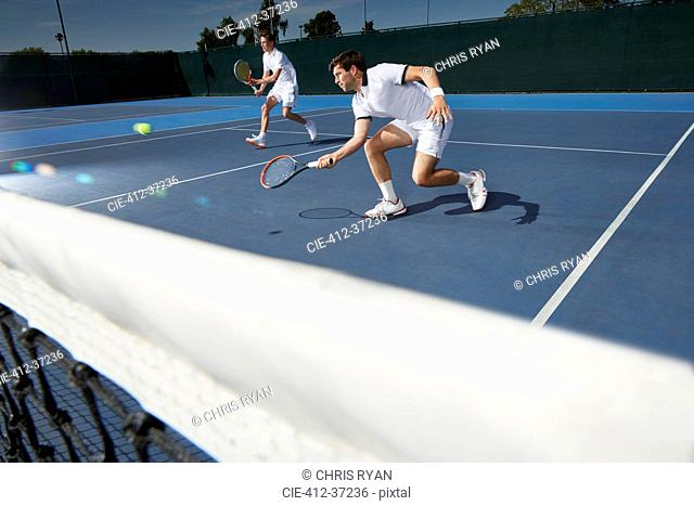 Young male tennis doubles players playing tennis on tennis court