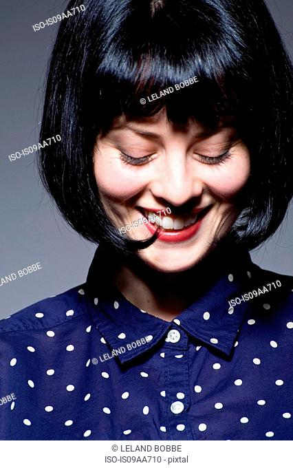 Young woman in blue spotted blouse looking down, smiling