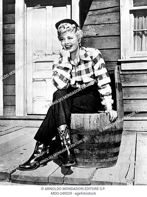 Shelley Winters dressed as a cowboy. US actress Shelley Winters posing smiling sitting on a barrel, dressed as a cowboy, with a plaid shirt, jeans and boots