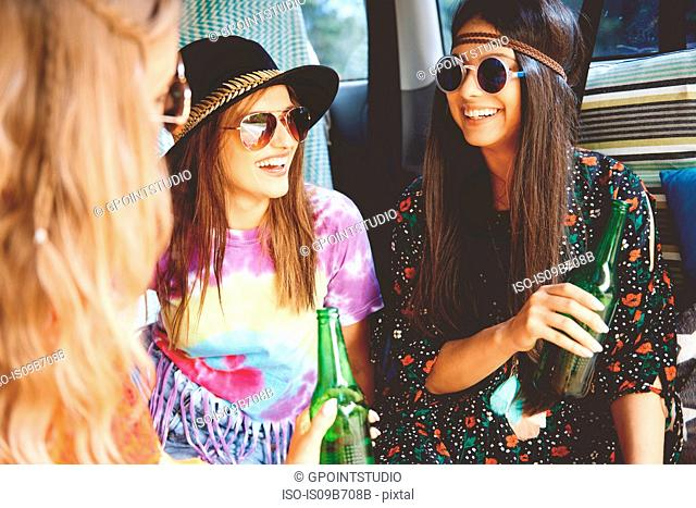 Three young boho women wearing sunglasses in recreational van