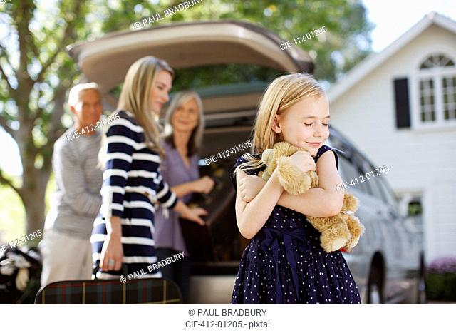 Girl hugging teddy bear outdoors