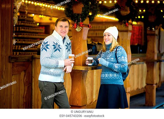 Eve of Christmas. Cute young couple has a good time at the Christmas bazaar. Young people stand near a wooden counter with paper cups in hands
