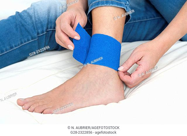Woman's foot and ankle with blue bandage strap