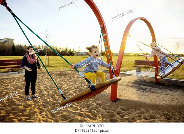 A young mom and her daughters playing on saucer swings in a playground on a warm autumn evening; Edmonton, Alberta, Canada