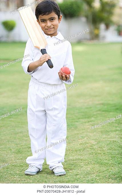Portrait of a boy holding a cricket bat and a cricket ball