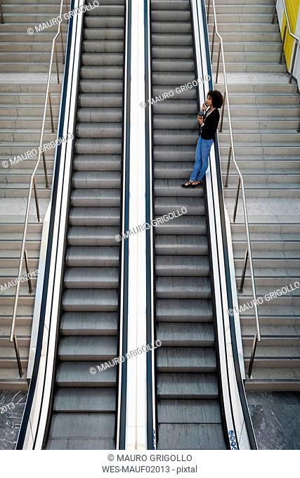Businesswoman on the phone standing on escalator