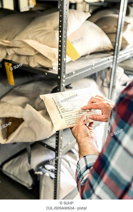Hand of scientist pointing at seed envelope in plant growth research centre warehouse