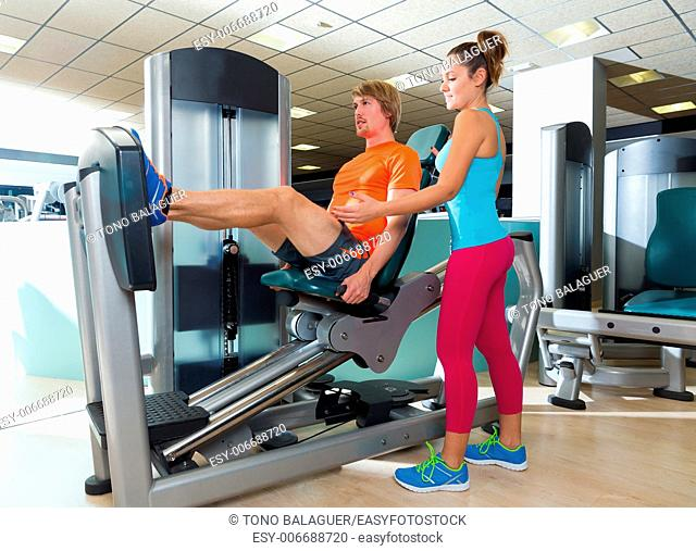 Gym seated leg press machine blond man workout and personal trainer woman