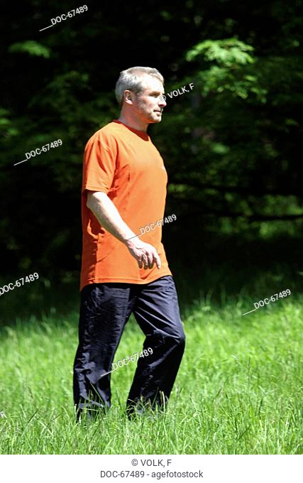 older man going fŸr a walk on a meadow wearing sport clothes