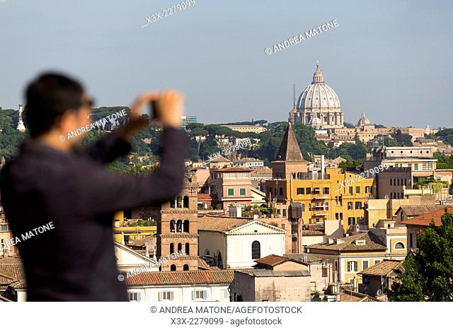 Taking a picture of the roman rooftops seen from Giardino degli Aranci. Rome, Italy