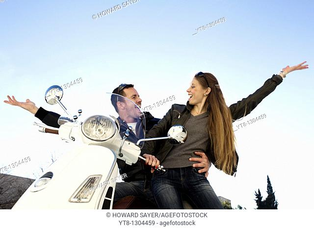 Couple sitting on a motor scooter and raising their arms in the air