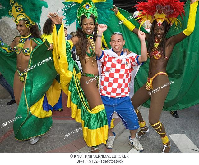 A Japanese soccer fan dancing with Brasilian samba dancers, Football World Cup 2006, Dortmund, North Rhine-Westphalia, Germany