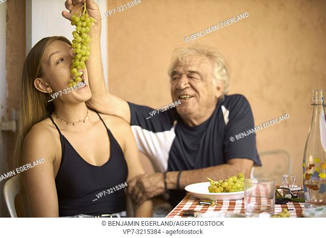 old senior man feeding young woman with wine grapes, sharing Greek tradition and healthy food, hospitality, grandfather, generous, In Chersonissos, Crete