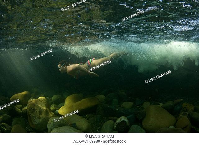 A girl swims underwater at Angel Falls near Courtenay, BC