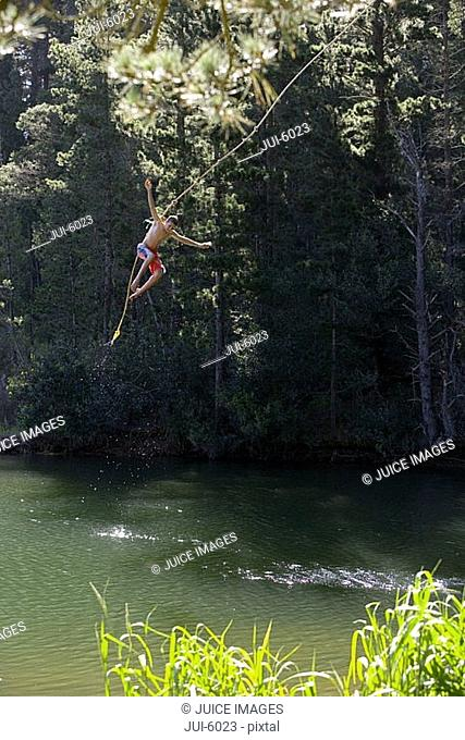 Boy 9-11, in swimming shorts, letting go of rope swing above lake