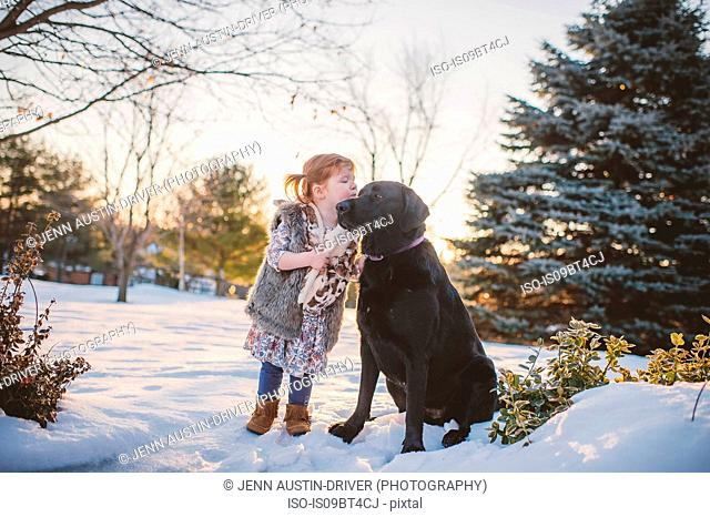 Female toddler with red hair playing in snow with dog, Keene, Ontario, Canada