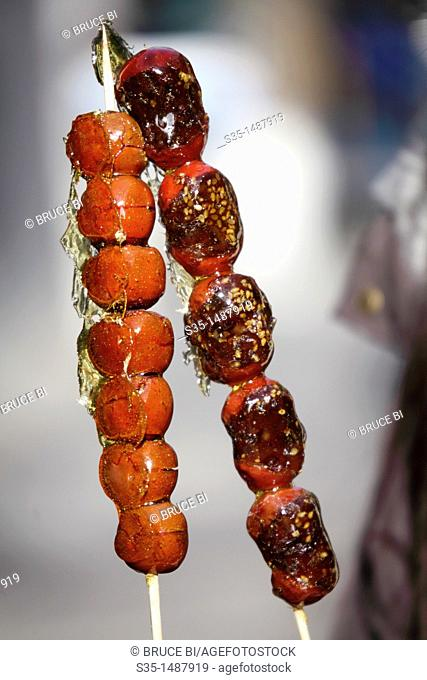 A closed up view of Sugar coated haws on a stick aka Sugar Gourd a traditional winter treat in Beijing  Beijing  China