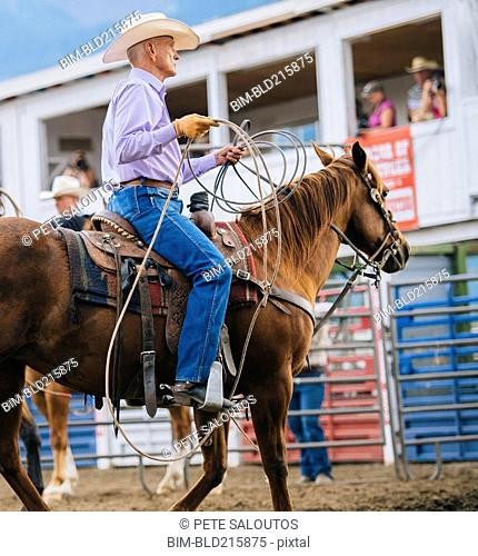 Caucasian cowboy riding horse in rodeo