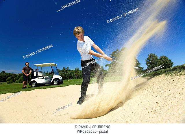 Golfer hits ball out of sand bunker whilst golfer with buggy looks on