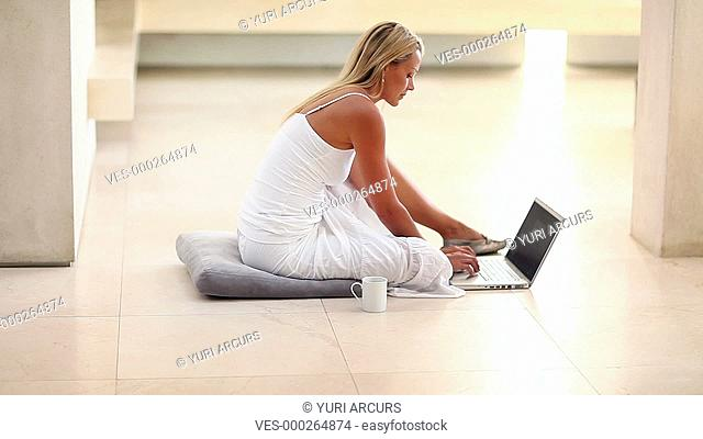 Beautiful woman typing on her laptop at home, looking up to smile at you