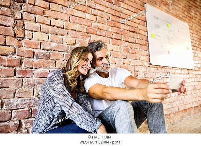 Businessman and woman sitting in their new office, sharing selfies