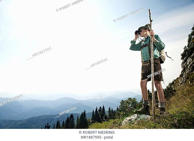 Germany, Bavaria, Boy looking through binoculars in the mountains