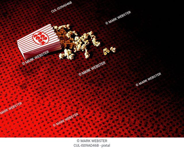 Spilled carton of popcorn on cinema carpet