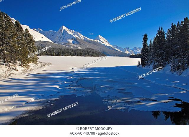 A horizontal winter landscape image of the open water outlet of Maligne Lake in Jasper National Park, Alberta, Canada