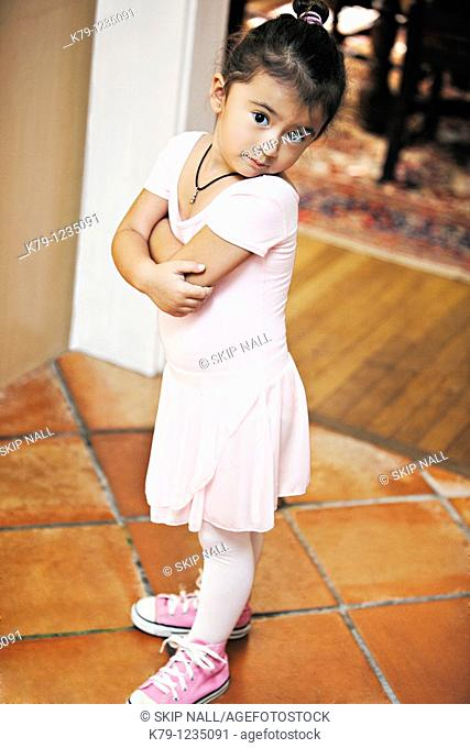 Little girl in ballet costume looking at camera